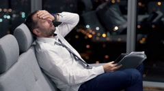 Tired, overworked businessman sitting on sofa at home at night Stock Footage
