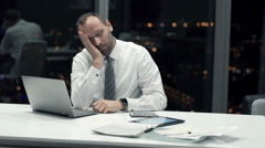 Tired businessman with laptop falling asleep on table in office at night Stock Footage