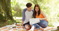 4k, Young couple reading newspaper while enjoying their day out in a park. Stock Footage