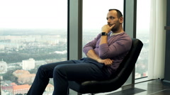 Pensive man sitting on chair and admire view from window at home Stock Footage