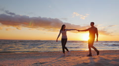 Steadicam slow motion shot: Romantic couple walking on the beach at sunset Stock Footage