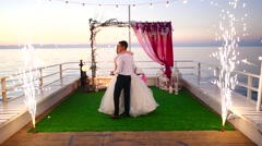 Bride and groom dancing on the sea Stock Footage