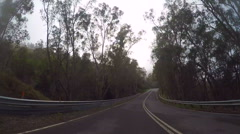 Winding mountain road through early morning mist. Arkistovideo