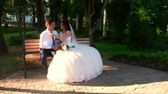 Bride and groom sit on the bench Stock Footage