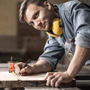Carpenter measuring wooden board Stock Photos