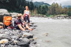 Two tourists refresh near the mountain river Stock Photos
