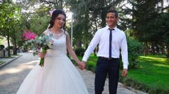 Bride and groom walking in park Stock Footage