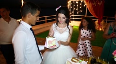 Bride and the groom feed each other cake Stock Footage
