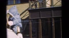 1951: man bounces and kisses baby in his arms before setting child down CHATHAM, Stock Footage