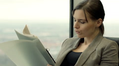 Elegant woman reading documents, bills sitting on chair by window at home Stock Footage
