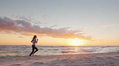Young attractive woman jogging on the beach at sunset Full length. Beautiful Stock Footage