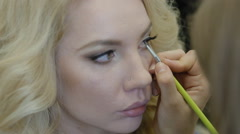 Make-up artist doing make-up model Stock Footage