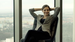 Portrait of happy, elegant woman sitting on chair by window at home Stock Footage