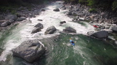 Kayaker Paddles Down River with Boulder Rapids Shot by Drone Stock Footage