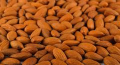 Pile of almonds close-up as abstract food background Stock Photos