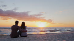 A young couple admiring the sunset at sea. Sit in an embrace on the sand Stock Footage