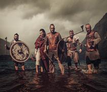 Mad vikings warriors, standing on the seashore with Drakkar on the background Stock Photos