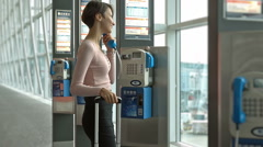 Beautiful business woman talking on a public phone at the airport. Stock Footage