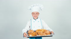 Portrait young baker holds oven-tray with pastries and gives you at camera Stock Footage