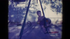 1958: children play on swings and cars in shadowy area near old tires  Stock Footage