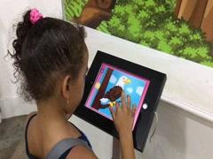 A girl taps an interactive panel at Kuala Lumpur Bird Park, Malaysia Stock Footage