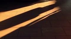 Feet walking on brown sunlit floor. 4K shot Arkistovideo