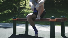 An unshaved man sitting on a bench and putting on an ankle support Stock Footage
