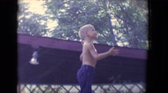 1958: a cute shirtless boy is reaching up over a fence and playing  Stock Footage
