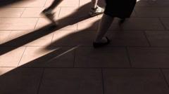 Preople walking on brown sunlit floor. 4K shot Arkistovideo