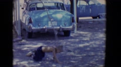1958: little boy on rope swing hits the ground in driveway TUCSON, ARIZONA Stock Footage