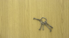Keyring with old house keys on wooden table Stock Footage