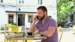 Man talking by smartphone during breakfast in cafe Stock Footage