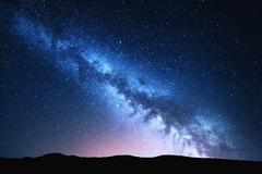 Milky Way and pink light at mountains. Night colorful landscape. Stock Photos
