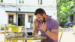 Angry man talking by smartphone during breakfast in cafe Stock Footage