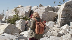 Couple Stepping Carefully on Rocks during Hiking Trip Stock Footage