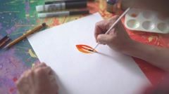 On a white sheet of paper unknown painting orange paint Stock Footage