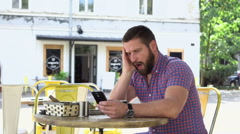 Bored, sleepy man drinks coffee browsing smartphone Stock Footage