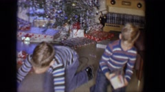 1958: twin brothers wearing striped shirts and blue jeans opening gifts  Stock Footage