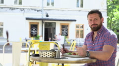 Man eating breakfast in cafe, slider shot, left Stock Footage
