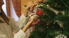 Closeup shot of beautiful girl hanging golden bauble on Christmas tree Stock Footage