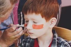 Child boy face painting, making tiger eyes process Stock Photos