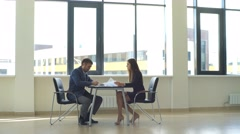 Businesswoman discussing work with a colleague at the table Stock Footage