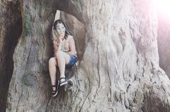 Girl child outdoors sit in tree with butterfly face painting Stock Photos