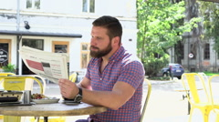 Man reading newspaper drinks coffee Stock Footage