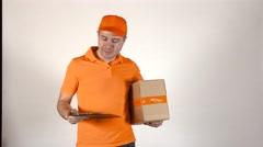 Courier in orange uniform delivering a parcel. Light grey backround, 4K studio Stock Footage
