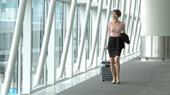 Woman walking in the airport with her trolley. Stock Footage