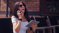Girl is talking on the phone and holding tablet pc. Stock Footage