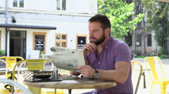 Man reading newspaper during breakfast and looks at camera Stock Footage