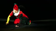 A man dressed in a jester costume is playing on a black background Stock Footage