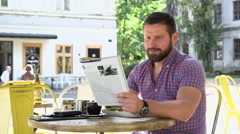Man reading magazine during breakfast Stock Footage